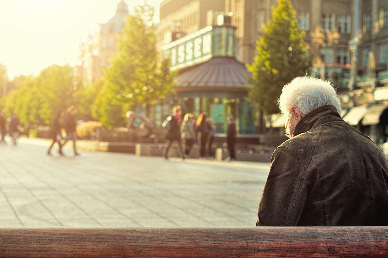 Ein alter Mann sitzt auf einer Bank