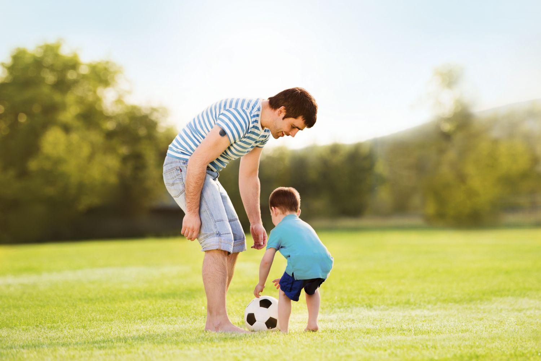 Ein Vater spielt mit seinem Sohn. Thema: Blutzucker messen