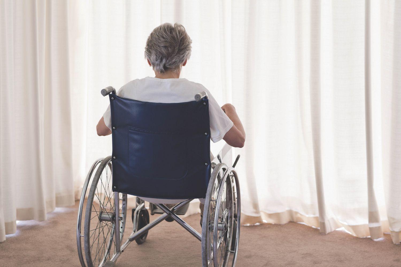 Eine Frau im Rollstuhl in der Rückenansicht